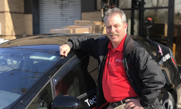 R.K. Black service technician Dwain Foss poses beside his R.K. Black Toyota Prius.