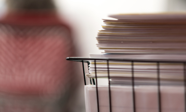 Image of stack of documents with office worker in background